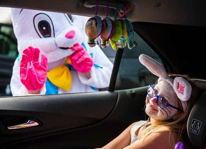 Six-year-old Vanessa Ferrigno of Ellwood City is all smiles as the Easter Bunny waves to her during a drive-through Easter egg hunt Saturday in Franklin Plaza.