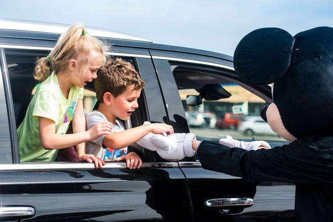 Lyric Kaszer, 6, left, of Ellwood City, and her cousin Braxon Baldelli, 3, of Zelienople, reach for candy offered by Mickey Mouse during a drive-through Easter egg hunt Saturday in Franklin Plaza.