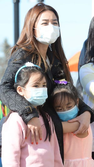 Randolph students will talk about racism during a Zoom forum April 27. Here, Thao Vu stands with daughters Sophia Lee, 6, and Crystal Lee, 6, during a Stop the Hate Peace Vigil against the rise in violence against Asian Americans, on the grounds of Stetson Hall in Randolph, on Saturday, March 27.