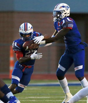 Hutchinson Community College's quarterback CJ Ogbonna (5) hands the ball to Anwar Lewis (25) during their game against Coffeyville  Friday night at Gowans Stadium. Hutchinson defeated Coffeyville 33-10.