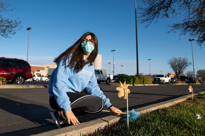 Noura Shoukfeh places a pinwheel outside of the 50th Street Market Street for Pinwheels for Prevention to raise awareness of child abuse on Saturday, March 27, 2021, in Lubbock, Texas.