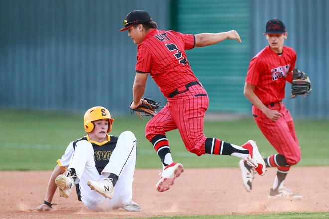 Levelland's Raymond Ochoa (3) attempts to tag Snyder's Dyllan Angeley (11) during a run-down on Friday, March 26, 2021, at Lobo Diamond in Levelland, Texas.