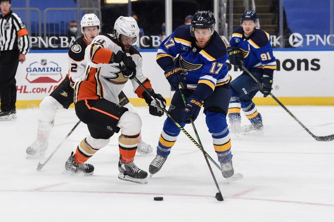 Anaheim Ducks' Adam Henrique (14) and St. Louis Blues' Jaden Schwartz (17) compete for the puck during the second period of an NHL hockey game Friday, March 26, 2021, in St. Louis.