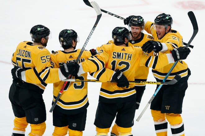 Boston Bruins' Craig Smith (12) celebrates his goal with teammates during the third period of an NHL hockey game against the Buffalo Sabres, Saturday in Boston.