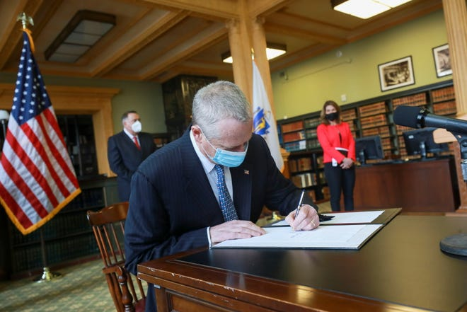 Gov. Charlie Baker signs new climate policy legislation Friday at the State House library.