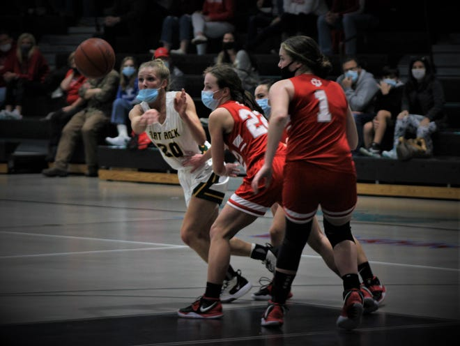 Flat Rock's Ryley Osentoski (left) passes around the defensive pressure from Grosse Ile's Natalie Christnagel (22) and Cailey O'Farrrell (1) on Friday, March 26, 2021 in the Division 2 District finals at Summit Academy.