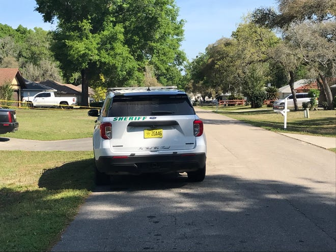 On Saturday, a sheriff's patrol vehicle remained parked outside the home where a body was discovered.