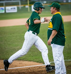 Forest's Tyler Rogers rounds third base as he gets a fist bump from the third base coach after hitting a two-run homer in the top of the 5th inning. The Wildcats defeated the North Marion Colts, 7-2, Friday night.