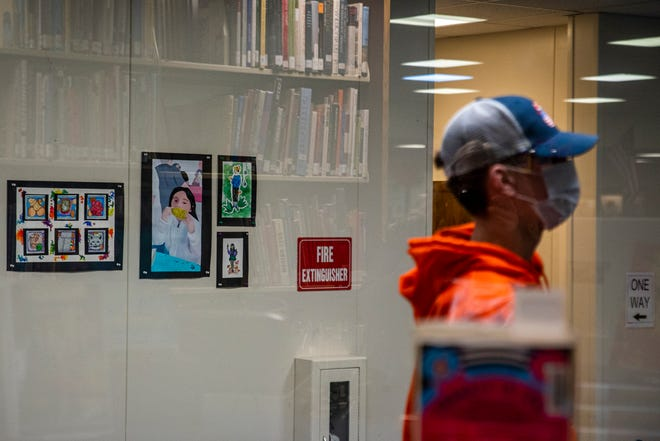 A collection of books is reflected in the glass, as a person walks near the York High School library on Friday, March 26, 2021. The school district is taking a variety of steps to assess and improve racial equity.