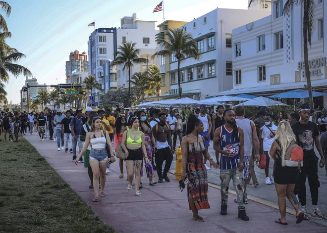 Spring break tourists walk alongside Ocean Drive in Miami Beach last week. An 8 p.m. curfew was extended in the city after law enforcement worked to contain unruly crowds. CARL JUSTE / THE MIAMI HERALD