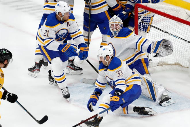Bruins forward Craig Smith, left, sends the puck through several Buffalo players and Sabres goaltender Linus Ullmark for the go-ahead goal during the third period of Saturday's game. Boston won, 3-2.