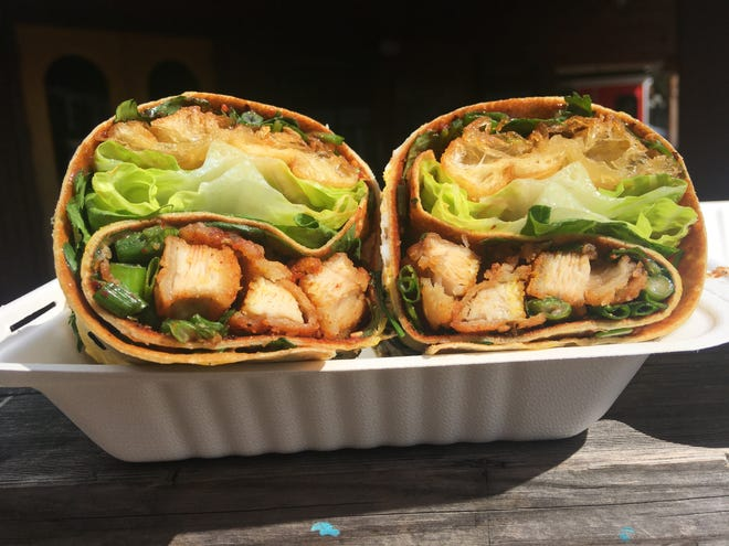 """A Bing King """"Nanjing Jianbing Old Street Original"""" consists of savory bean paste, cilantro, green onions, romaine lettuce, a fried egg, toasted sesame and crispy fried youtiao dough bread, with spicy Sichuan chicken included inside."""