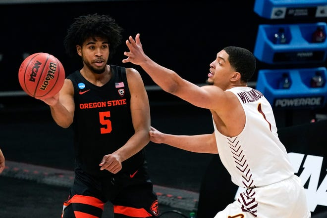 Oregon State guard Ethan Thompson (5) passes around Loyola Chicago guard Lucas Williamson  during the first half of Saturday's NCAA Tournament at Bankers Life Fieldhouse in Indianapolis.