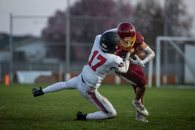 Junction City's Gabe Ward tries to run over Santiam Christian's Jackson Risinger (17) during their March 26 game. Ward ran for 261 yards in the rematch on Friday as the Tigers won 42-13.