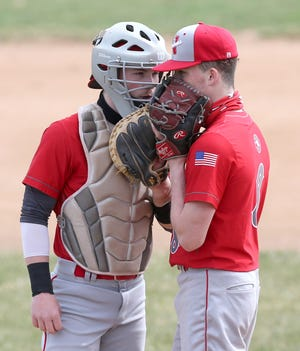 Jordan Mick (left) and his brother Braden Mick of Northwest meet on the mound during their game at GlenOak on Saturday, March 27, 2021.