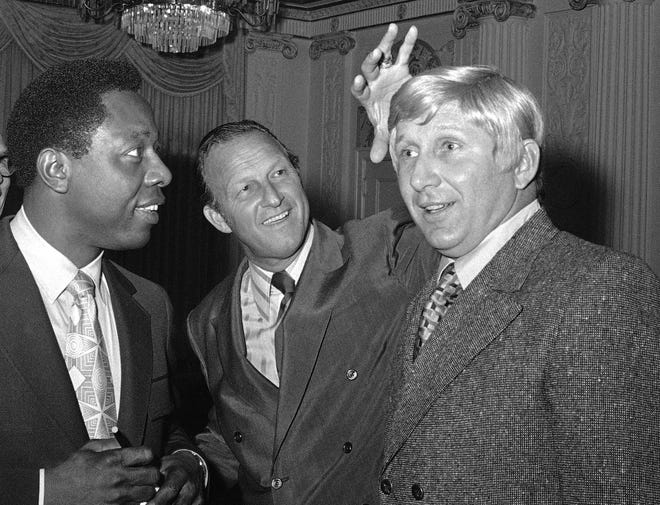 Stan Musial, center, vice president of the St. Louis Cardinals, jokes around as he reaches to feel a blond wig worn by Joe Cunningham, right, manager of the Cardinals, as Atlanta Braves' Hank Aaron, left, watches in St. Petersburg, Fla., in 1971.