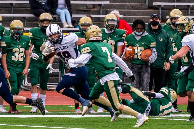 Apponequet's Kevin Hughes sprints along the sidelines eyeing GNB Voc-Tech's Lucas Dacosta.