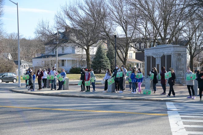"""Residents, neighbors, parents and Doherty Memorial High students hold """"Share Duffy Field"""" signs Saturday in Worcester's Newton Square to show their support for a plan to renovate the playing fields there."""