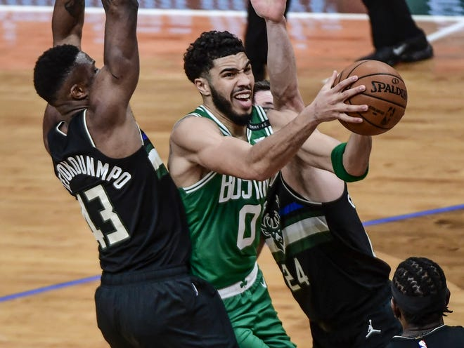 Celtics forward Jayson Tatum splits the defense while driving toward the basket during Friday night's game against the Bucks in Milwaukee.