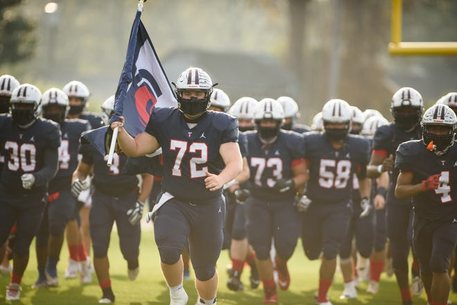 Senior Hayden Honeycutt leads the Bulldogs onto the field before the Pine Forest at Terry Sanford football game on Friday, March 26, 2021.