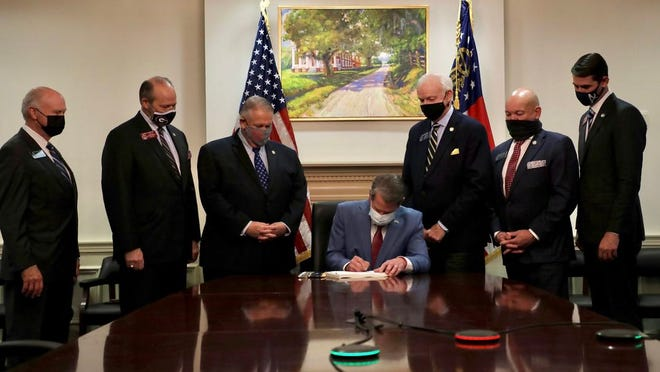 Georgia Gov. Brian Kemp signs into a law a new bill that restricts voting procedures on Thursday, March 25, 2021. The law has drawn condemnation from across the nation and has been called 'Jim Crow 2.0,' because critics say it targets Black voters and voting rights.