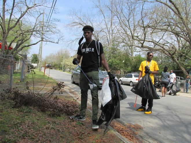 Fayetteville boxer Michael Williams Jr. helps clean up the Massey Hill neighborhood in Fayetteville on Saturday, March 27, 2021.