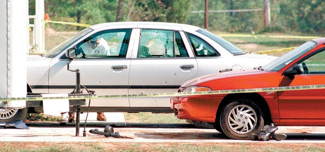 Cars riddled with bullets are seen after a man engaged in a shootout with police in Rainbow City on Oct. 10, 1997. Gary Entrekin, one of the men wounded in the incident and the man who was able to radio for help during the shooting, passed away Friday.
