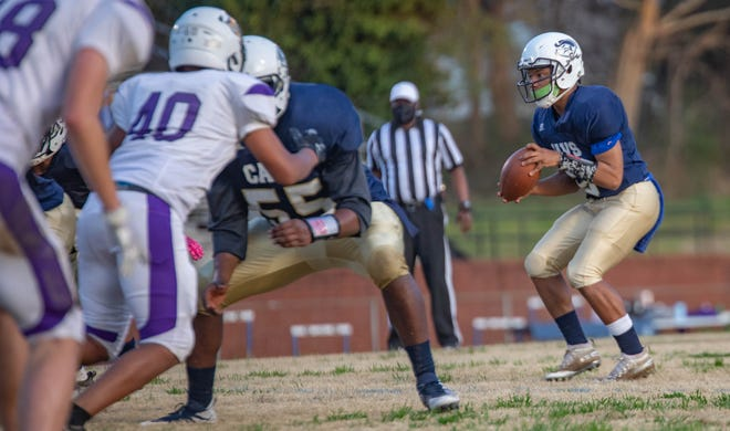 Cummings quarterback Tylek Oliver receives a snap against Carrboro. Oliver finished with a school-record eight touchdown passes, one shy of the NCHSAA record for most touchdown passes in a single game.