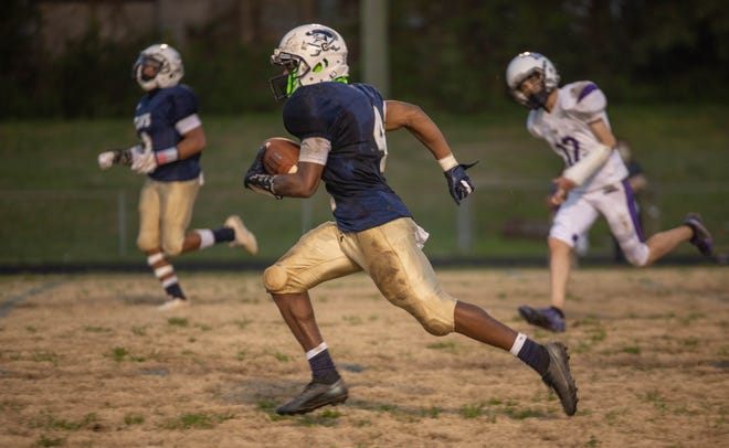 Cummings wide receiver Dylantae James (4) runs with the ball against Carrboro during a March 26, 2021, home game. James has picked some late recruiting interest this fall as his senior season wraps up.