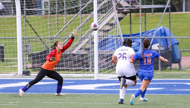 ACA's Gracie Olsen (12) shoots the ball over the reach of Holt goalkeeper Wendy Barrientos (14). ACA women's soccer defeated Holt by mercy rule 10-0 on March 26, 2021 [Photo/Hannah Saad]