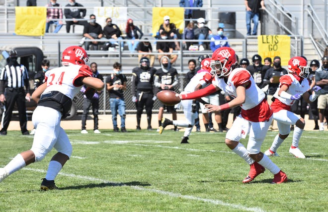 Oak Hills quarterback Andrew Garcia hands off the ball during the second quarter against Hesperia on Saturday, March 27, 2021.