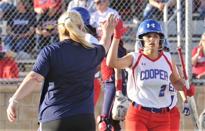 Cooper coach Stacey Herring, left, high fives Jahlissah Marquez (2) after Marquez and Ailyah Martinez scored in the first inning against Lubbock Monterey.