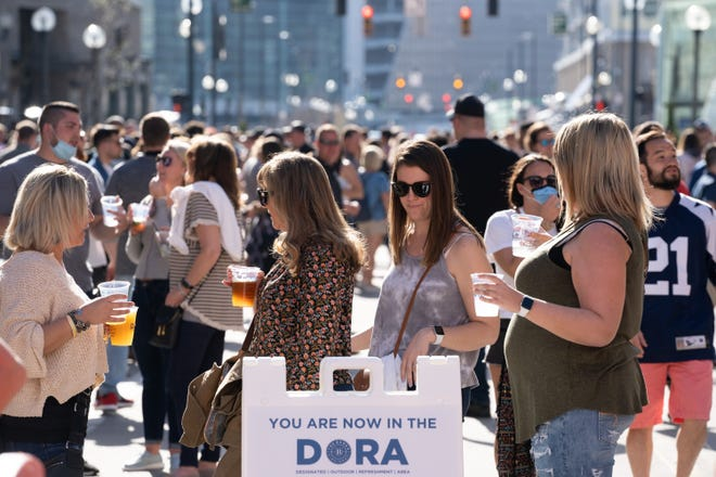 People look at the new Dora sign as they walk around The Banks, Saturday, March 27, 2021 in Cincinnati, Ohio. Dora stands for Designated Outdoor Refreshment Area and just started in The Banks on Thursday.