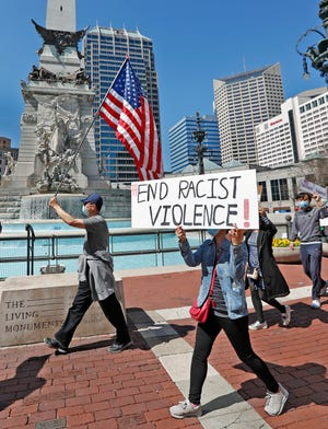 """Protesters gather during the """"Indiana Stop Asian Hate Rally,"""" Saturday, March 27, 2021 on Monument Circle in Indianapolis. The Asian American Alliance Inc. and Indianapolis Chinese Center Community Inc. put on the rally and vigil on this national day of action demanding an end to anti-Asian racist violence, an end to violence against women and an end to white supremacy."""