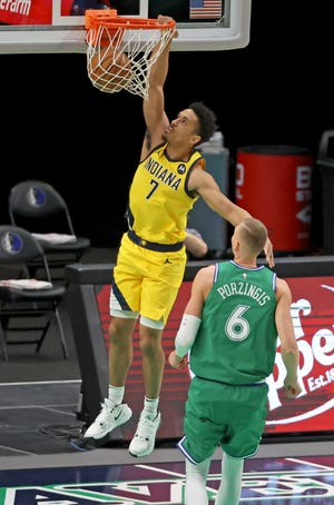 Mar 26, 2021; Dallas, Texas, USA;  Indiana Pacers guard Malcolm Brogdon (7) dunks past Dallas Mavericks center Kristaps Porzingis (6) during the first quarter at American Airlines Center. Mandatory Credit: Kevin Jairaj-USA TODAY Sports