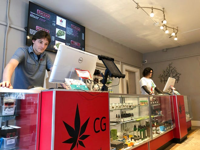 In this March 6, 2019, file photo, Korbin Osborn, left, works as a cannabis adviser at a medical marijuana dispensary in Santa Fe, N.M. Legislation to legalize cannabis in New Mexico advanced Thursday, March 18, 2021, toward a decisive Senate floor vote under a framework that emphasizes government oversight of pricing and supplies and social services for communities where the criminalization of pot led to aggressive policing.