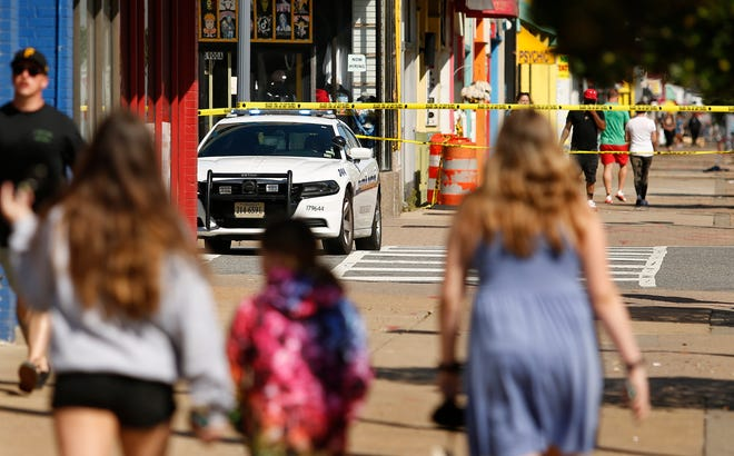 Tourists navigate police tape blocking several streets along the Virginia Beach Oceanfront on Saturday, March 27, 2021, the morning after a fatal shooting in Virginia Beach, Va.