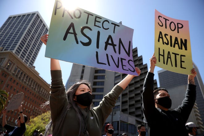Demonstrators hold signs during a rally to show solidarity with Asian Americans at Embarcadero Plaza on March 26, 2021, in San Francisco.