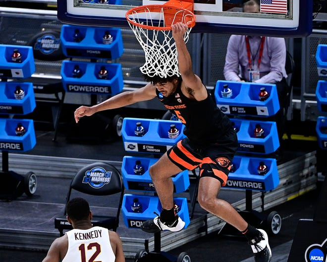 Oregon State guard Ethan Thompson hangs on the rim after dunking against Loyola Chicago during their Sweet 16 game.