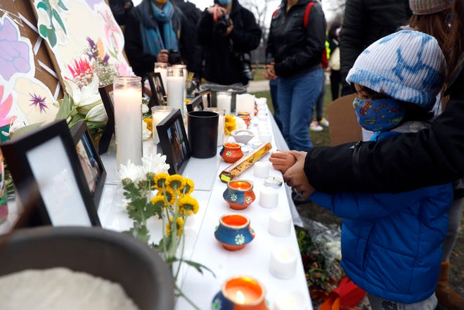 A child lights a candle at a makeshift memorial during a vigil and rally against Asian hate crimes, Friday, March 26, 2021, at Chicago's Horner Park. The event is organized by local Chicago organizations led by Asian Americans and Pacific Islanders. (AP Photo/Shafkat Anowar)