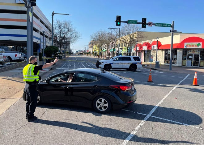 Virginia Beach police redirect traffic on Saturday, March 27, 2021 after late night shootings as they investigate a late night shooting in Virginia Beach, Va.