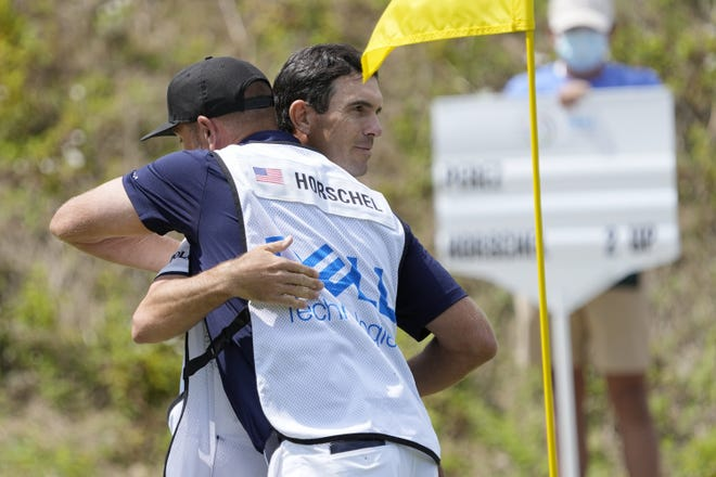 Billy Horschel gets a hug from his caddie on the No. 16 green after winning his semifinal round match against Victor Perez, of France, at the Dell Technologies Match Play Championship golf tournament Sunday,