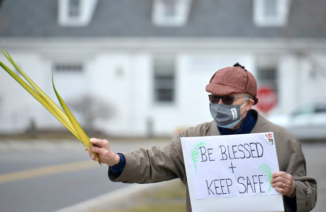 Steve Washburn directs traffic near First Congressional Church, UCC in Harwich Center, Massachusetts, on March 28, 2021. Washburn is the husband of the church's interim pastor, the Rev. Dianne Arakawa. Church leaders have struggled with declining attendance and offerings during the COVID-19 pandemic.  Merrily Cassidy/Cape Cod Times