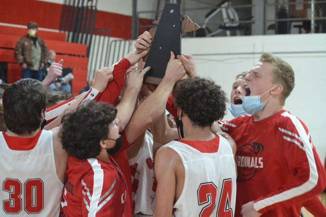 Onaway boys basketball players celebrate with the trophy after defeating Hillman in a Division 4 district final in Onaway on Saturday.