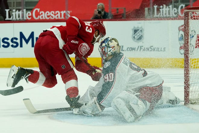 Elvis Merzlikins (90) stops a shot by Detroit Red Wings left wing Darren Helm (43) during the second Sunday at LIttle Caesar's Arena in Detroit.