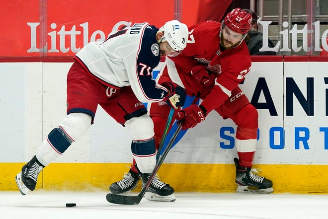 Nick Foligno (71) and Red Wings center Michael Rasmussen (27) try controlling the puck during the third period of the Blue Jackets' 3-1 loss Saturday at Little Caesar's Arena in Detroit.