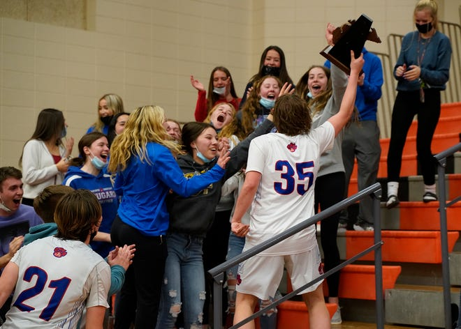 Lenawee Christian senior Jude Mineff (35) celebrates with the LCS student section after the team won the Division 3 district championship over Hudson Saturday night. Mineff hit the winning shot with less than 20 seconds to go in the Cougars' 58-56 victory.