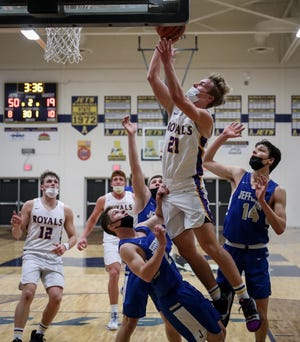 Blissfield's Owen Smith drives to the basket over Monroe Jefferson's Kline Peare (left), Shea Peare and Ryan Gennoe, Saturday evening during the second quarter of the District Final. [Photo by DANA STIEFEL]