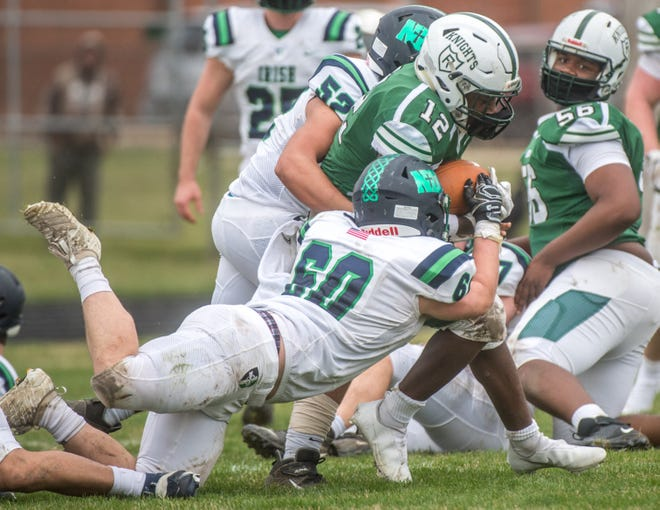 Peoria Notre Dame's James Hodskins (60) and Miko Flores (52) chase down a Richwoods running back during a game last season at Richwoods. The two-way players also anchor the line at guard for the Irish.