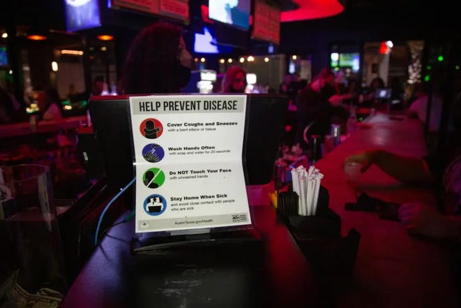 A sign asks customers to follow COVID safety precautions at the Green Light Social bar in Downtown Austin on March 12. Economists say that the state's economic recovery will largely depend on how safe Texans feel in public as the pandemic persists.